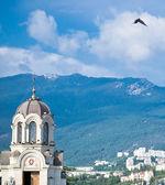 Kyrkan på en bakgrund av berg med en fågel svävande i himlen — Stockfoto