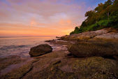 Phuket beach at Sunrise with interesting rocks in foreground — Stock Photo