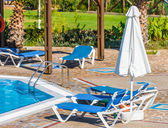 Swimming pool with sun loungers — Stok fotoğraf