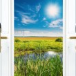 Open door with a view of green meadow illuminated by bright sunshine — Stock Photo #37830255