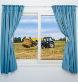 Tractor hay removes the view from the window with curtains — Stock Photo