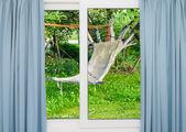 窓にカーテンのハンモックで庭を見下ろす — ストック写真