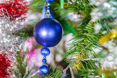 Christmas decorations hanging on a pine tree with glitter, — Stock Photo