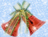 Christmas bells with bow on shiny background snowflakes — Stock Photo