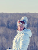 Middle-aged brunette on a hillside in a cap and ski goggles — Stock Photo