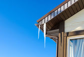 Roof of the house with hanging icicles on blue sky background — ストック写真