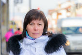 Brunette middle-aged woman in a stylish white jacket with fur hood — Stock Photo