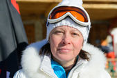 Middle-aged woman in a white jacket and ski goggles — Stock Photo