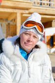 Middle-aged woman in a white jacket ski glasses — Stock Photo