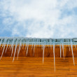Roof of the house with hanging icicles on blue sky background — Stock Photo #42307885
