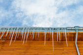 Roof of the house with hanging icicles on blue sky background — Stock Photo