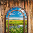 Open door with a view of green meadow illuminated by bright suns — Stock Photo #42519825