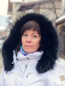 Brunette middle-aged woman in a stylish white jacket with fur ho — Stock Photo