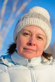 The woman of average years in a white knitted cap — Stock Photo
