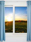 Open door with a view of green meadow illuminated by bright sunshine — Stock Photo