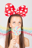 Young woman with colorful lollipop and big dotty bow — Stock Photo