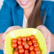 Happy young woman holding a bowl full of cherry tomatoes — Stock Photo