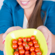 Royalty-Free Stock Photo: Happy young woman holding a bowl full of cherry tomatoes