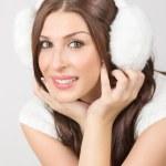 Beautiful young woman wearing white earmuffs — Stock Photo