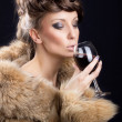 Gorgeous woman in luxurious fur drinking wine — Stock Photo