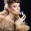 Gorgeous woman in luxurious fur drinking wine — Stock Photo #17079501
