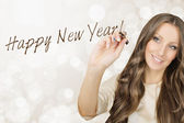 Beautiful businesswoman writing Happy New Year — Stock Photo