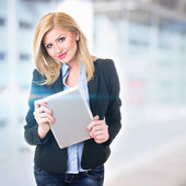 Attractive businesswoman in front of office holding digital tablet — Stock Photo