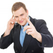 Young businessman talking on the phone pointing with finger — Stock Photo #25158703