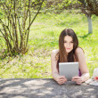 Young woman using digital tablet outdoors on summer day — Stock Photo #25376219