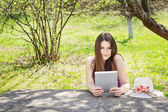 Young woman using digital tablet outdoors on summer day — Stock Photo