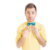 Surprised young man wearing yellow shirt and green bowtie — Stock Photo
