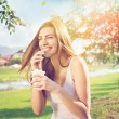 Beautiful happy young woman drinking coffee in park — Stock Photo