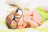Cute baby boy with eyeglasses and books — Stock Photo