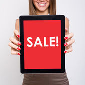 Beautiful young woman showing tablet screen that states sale — Stock Photo