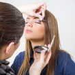Makeup artist applying eyeshadow to a model — Stock Photo #29378303