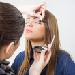 Makeup artist applying eyeshadow to a model — Stock Photo