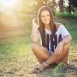 Cute young woman enjoying in park on sunny day — Стоковая фотография