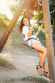 Young woman on the swing in park — Stock Photo