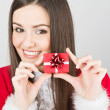 Happy young brunette woman holding a small present — Stock Photo