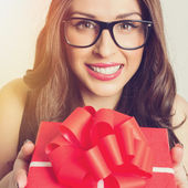 Big smile young woman with red present — Stock Photo