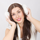 Happy young brunette woman wearing ear muff — Stock Photo
