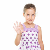 Cute little girl in dotted dress showing five fingers — Stock Photo