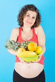 Happy pregnant woman with healthy fruits over blue background — Stock Photo
