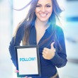 Cute young woman holding tablet that states follow — Stock Photo