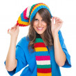 Cute young woman wearing colorful winter hat and scarf — Stock Photo #31976529