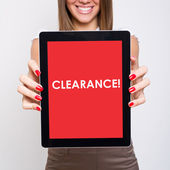 Young woman holding tablet computer that states clearance — Stock Photo