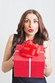 Donna giovane sorpreso mostrando grande rosso regalo — Foto Stock