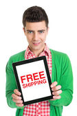 Young man holding a tablet that states free shipping — Stock Photo