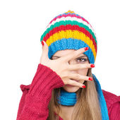 Young woman wearing colorful hat hiding behind her hand — Stock Photo