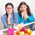 Two cute teenage schoolgirls studying together — Stock Photo